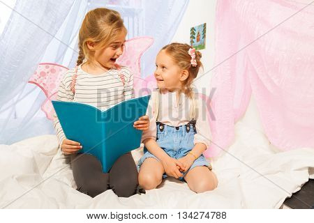 Two happy girls in costumes of little pixies with pink wings, reading bedtime story