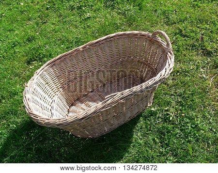 empty wicker laundry basket lying in the grass