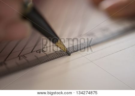 Close up of a mechanical pencil tracing a line on paper with a ruler