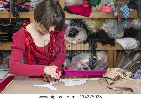A seamstress in red blouse and necklaces measuring and cutting white cloth on cutting table.