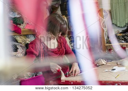 A seamstress in red blouse and necklaces measuring and cutting white cloth on cutting table with ribbons in the foreground.