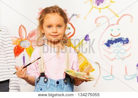 Cute smiling painter, five years old girl with brush and pallet drawing colorful picture