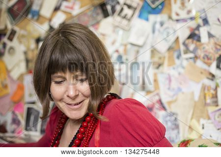 A lady in red blouse and necklaces smiling and staring below with wall of photos and cards in the background.