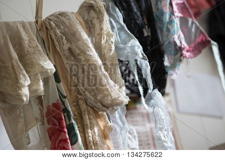 A collection of lace fabric of various colors and designs on a clothesline.
