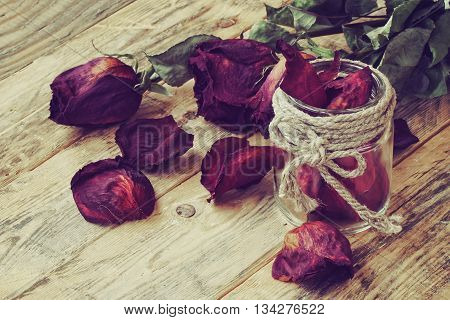bouquet of dried purple roses and glass jar with petals on the wooden table