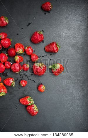 top view of fresh strawberry harvest nicely scattered on black table