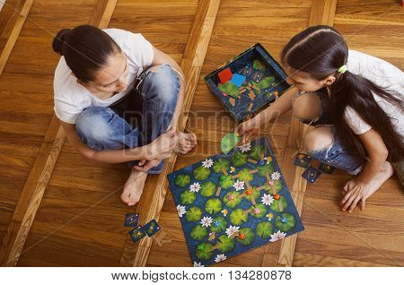 top view of mother and daughter playing a board game