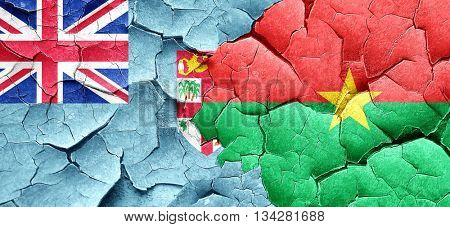 Fiji flag with Burkina Faso flag on a grunge cracked wall