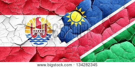 french polynesia flag with Namibia flag on a grunge cracked wall