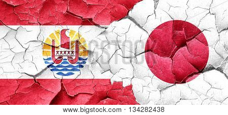 french polynesia flag with Japan flag on a grunge cracked wall