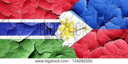 Gambia flag with Philippines flag on a grunge cracked wall