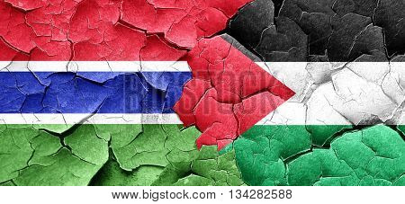 Gambia flag with Palestine flag on a grunge cracked wall