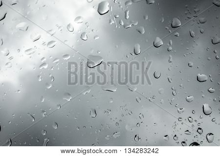 Raindrops on a car window pane on a cloudy day
