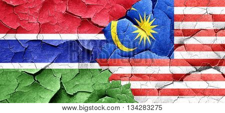 Gambia flag with Malaysia flag on a grunge cracked wall