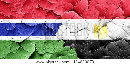 Gambia flag with egypt flag on a grunge cracked wall