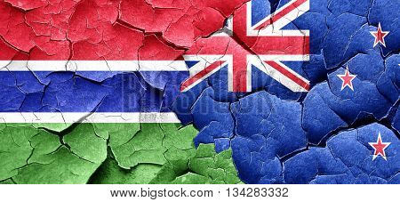 Gambia flag with New Zealand flag on a grunge cracked wall