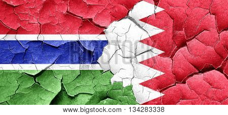 Gambia flag with Bahrain flag on a grunge cracked wall