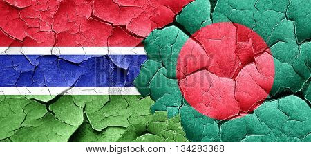 Gambia flag with Bangladesh flag on a grunge cracked wall