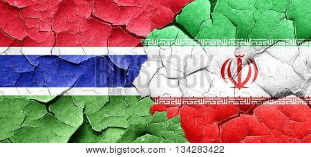 Gambia flag with Iran flag on a grunge cracked wall