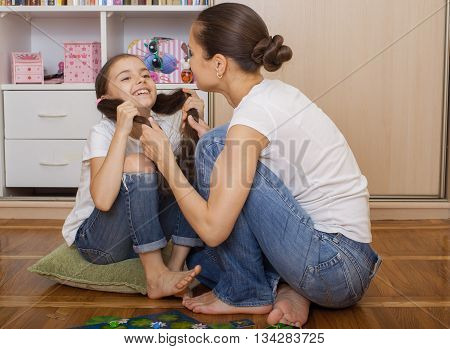Mom and daughter having fun sitting on the floor