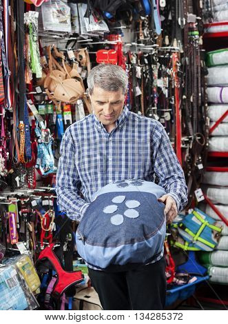 Man Examining Pet Cushion In Store