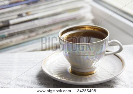 Morning cup of coffee (espresso) and ream of newspapers
