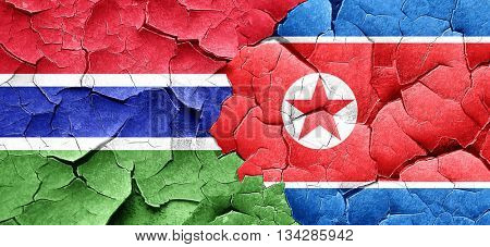 Gambia flag with North Korea flag on a grunge cracked wall