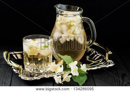Refreshing cold green tea with jasmine and ice in a jug and a glass