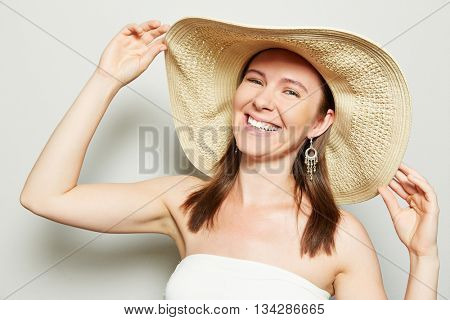 Smiling happy woman holding brim of straw hat with her hands