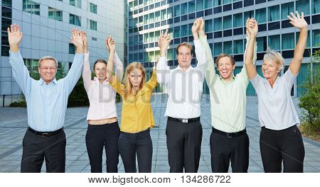 Motivated business people team raising arms up together