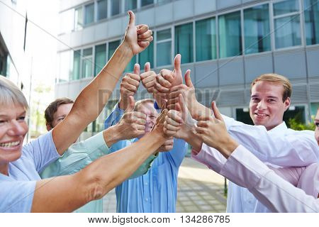 Successful group of business people holding their thumbs up