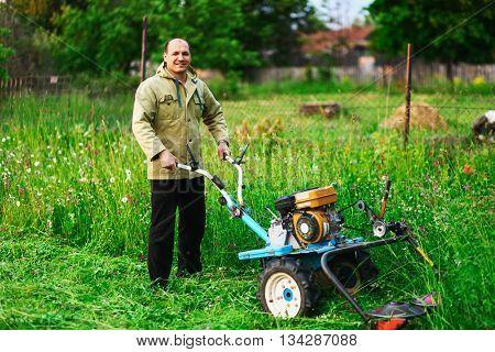 A Man Mowing The Grass.