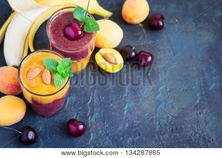 Fresh seasonal colorful Smoothies of apricot and sweet cherry on a dark background. Top view with copy space. Selective focus