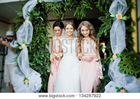 Smiled Bride With Bridesmaids Under Decor Pine Arch