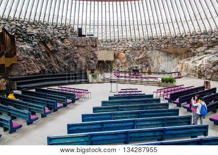 HELSINKI, FINLAND - circa MARCH 2016: Tourists inside of the rock church (Temppeliaukio) in Helsinki, Finland. The rock church is a popular sightseeing spot for tourists.