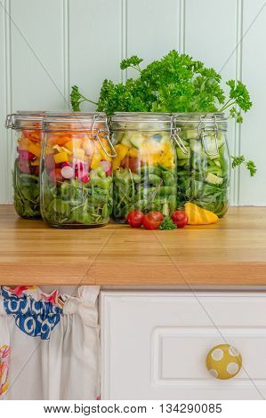 Prepared salad in glass storage jars on a kitchen work surface. Vertical.