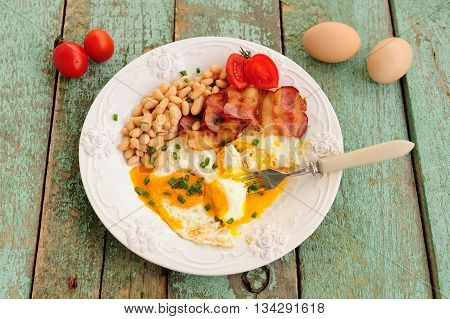 Homemade breakfast of fried eggs bacon beans and tomatoes on wooden table horizontal