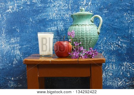 Still life with apple milk and flowers. On a stool on a blue background - a jug and a glass of milk an apple and a bouquet of wildflowers.