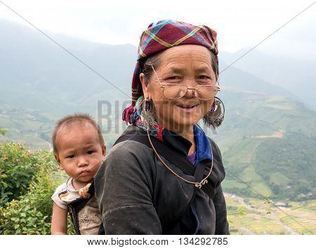 YEN BAI, VIETNAM, September 12, 2015 Mrs. Grandson piggyback on his back, the high mountains, Yen Bai