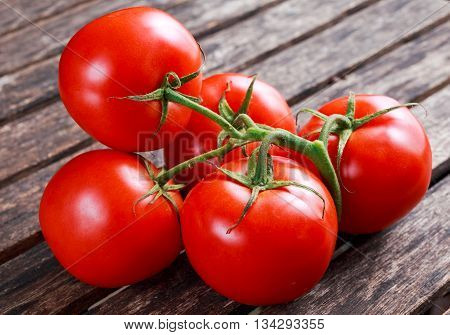 Organic Vine ripe tomatoes on wooden table.
