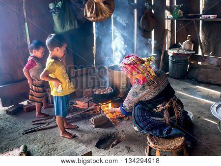 YEN BAI, Vietnam, September 12, 2015 Grandmother and grandchildren, ethnic Hmong, high mountains, Yen Bai province, cooking, the simple house
