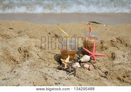 Cold coffee frappes set on beach with sea stars shells and grass with sea foam in background