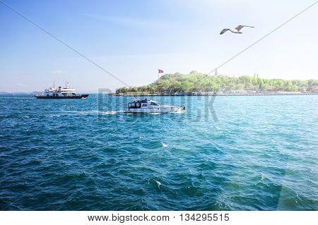 Island in sea with ships under bright sun