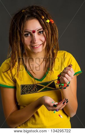 portrait of a beautiful young woman with dreadlocks on a gray background
