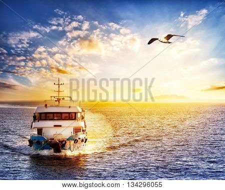 Ship at sea with an island on sunset