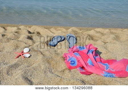 Pair of blue flip flops on a beach with sea in background