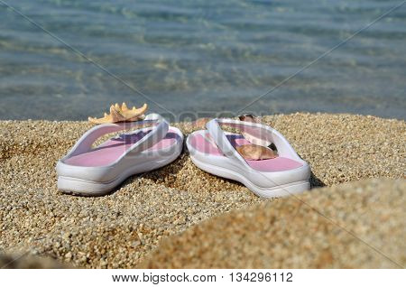 White-pink flip flops on beach with sea in background