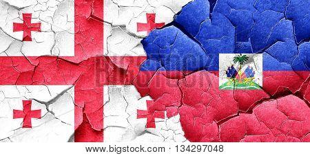 Georgia flag with Haiti flag on a grunge cracked wall
