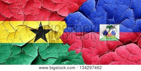 Ghana flag with Haiti flag on a grunge cracked wall