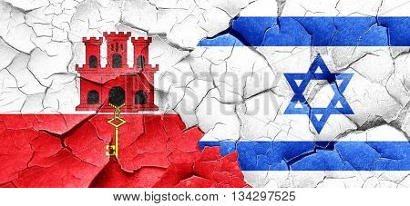 gibraltar flag with Israel flag on a grunge cracked wall